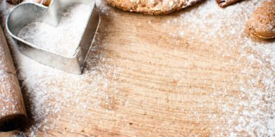 16018875-Christmas-and-holiday-baking-background-flour-bakeware-heart-cinnamon-cookies-and-almonds-on-a-woode-Stock-Photo