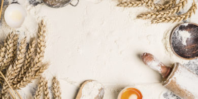 flour baking background with raw egg, rolling pin and wheat ear , top view